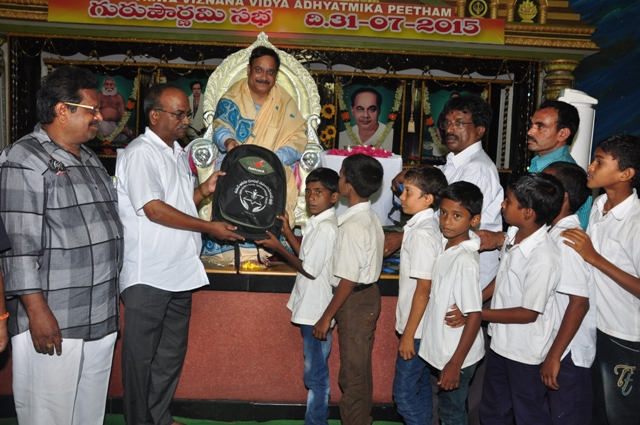 Dr.Umar Alisha, UARDT chairman, ​distributing school bags to 125 students of R.R.BH.R BC boys hostel pithapuram on the occasion of Guru Pournami at Sri Viswa Vizanan Aadhyatmika Peetham new Ashram Premises