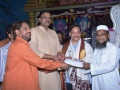 Sathguru Presenting Cheque to poor people along with V.V.Lakshmi Narayana and Sri Ahammad Alisha via U.AR.D.T