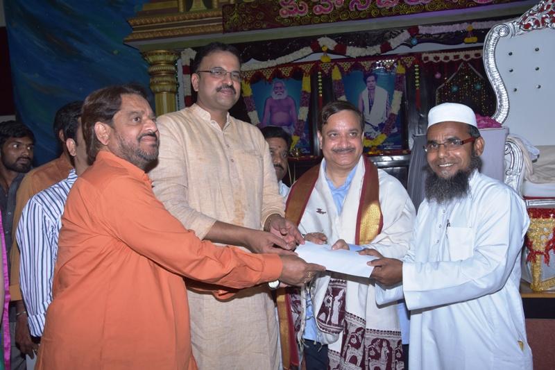 Sathguru Presenting Cheque to poor people along with V.V.Lakshmi Narayana and Sri Ahammad Alisha via U.AR.D.T
